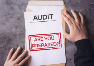 Audit Envelope Are You Prepared on white paper an yellow envelope holding by human hands